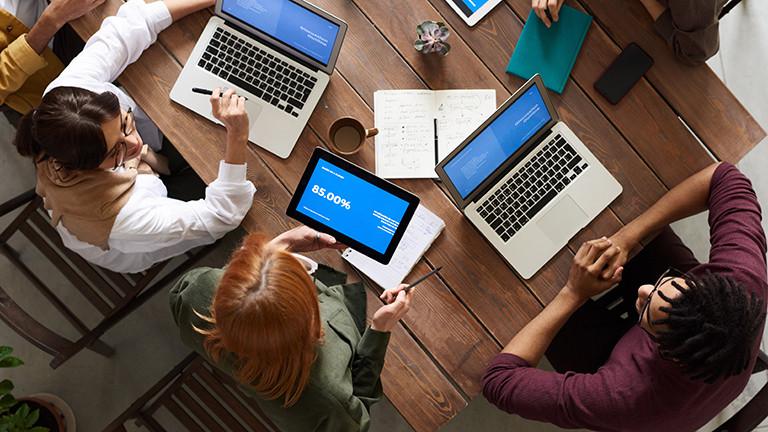 Verschiedene Mitarbeiter einer Firma sitzen an einem Konferenztisch.