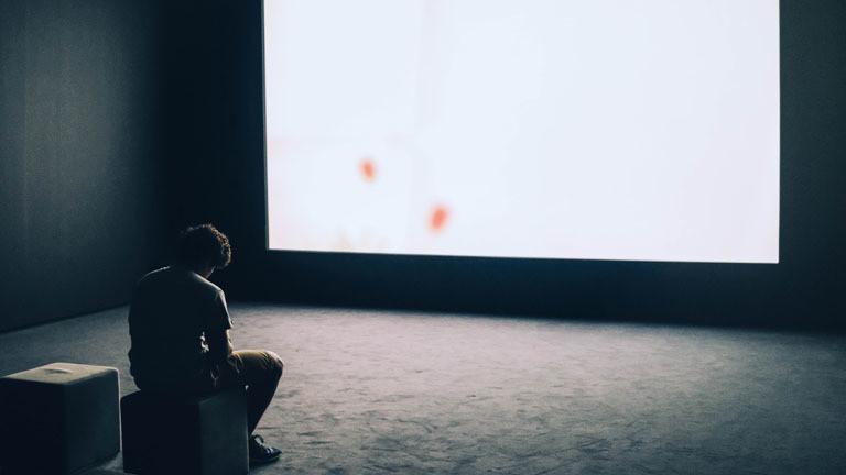 Ein Mann sitzt alleine vor einer weißen Leinwand.