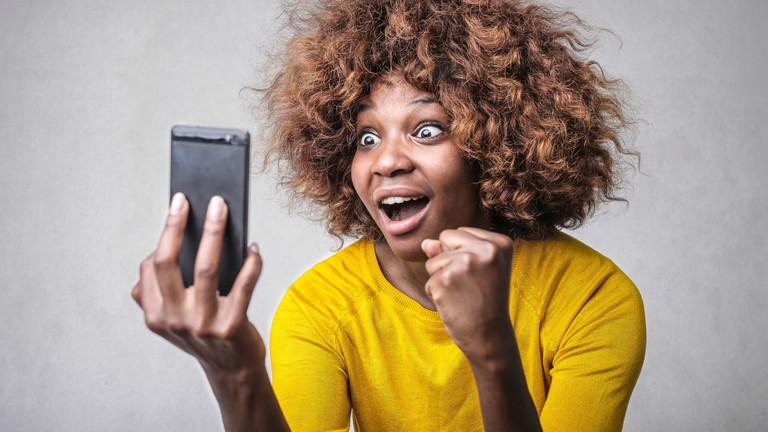 Eine Frau schaut auf ihr Smartphone und freut sich.