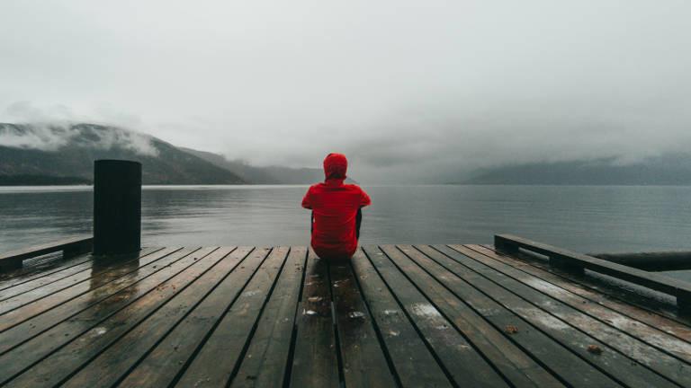 Person sitzt auf Steg am Wasser