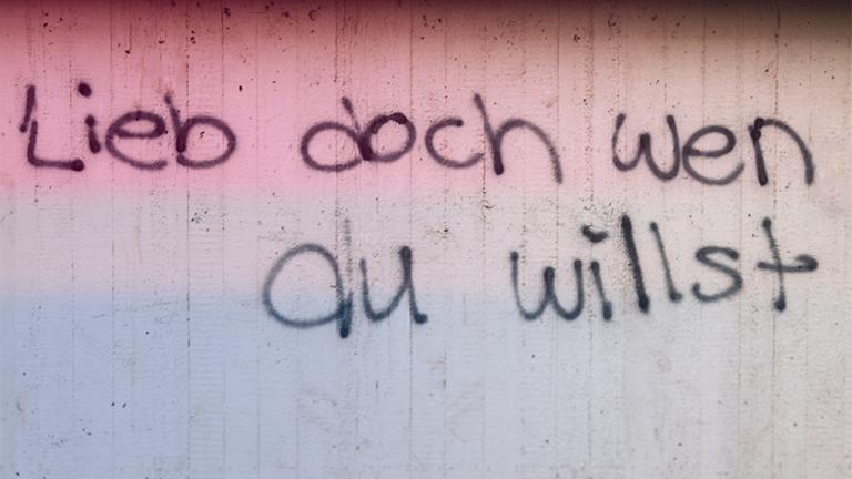 """Graffiti mit dem Schriftzug """"Lieb doch, wen du willst"""" an einer Hauswand, überlagert von einer Bisexualitäts-Flagge"""
