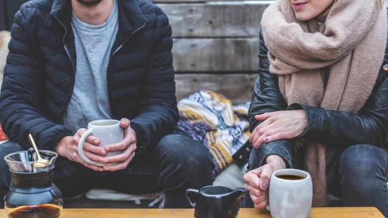 Ein Paar sitzt mit etwas Abstand nebeneinander und trinkt Kaffee.
