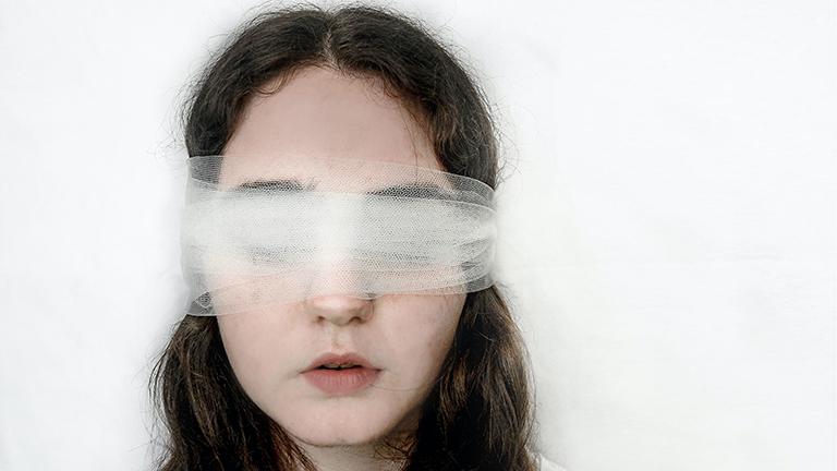 Eine junge Frau hat die Augen mit einem transparenten weißen Tuch verbunden.