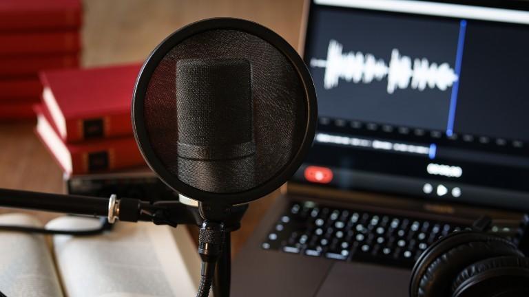 Podcasteqipment: Mikrophon, Laptop, ein Buch.