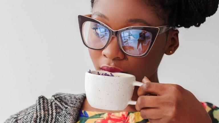 Eine Frau trinkt Kaffee und guckt durch eine stylishe Brille skeptisch in die Kamera.