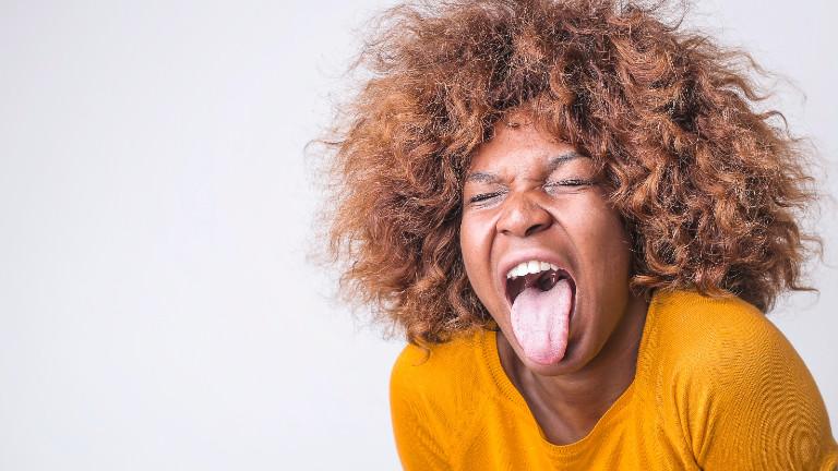 Eine Frau streckt vor Ekel die Zunge heraus.