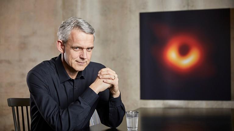 Astrophysiker Heino Falcke neben dem Bild, das das schwarze Loch zeigt.