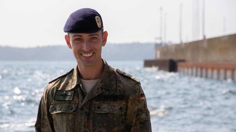 Fabian Scharf ist Minentaucher - er steht in Uniform vor dem Meer.