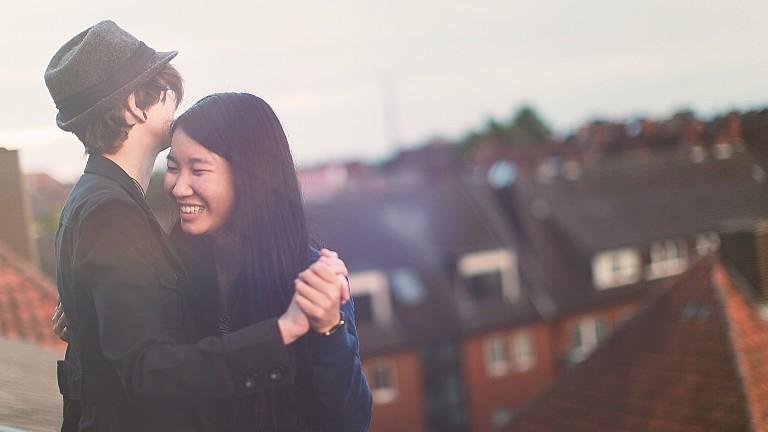 Eine Frau und ein Mann tanzen auf einem Hausdach.
