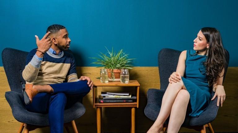 Mann und Frau sitzen sich gegenüber und unterhalten sich.