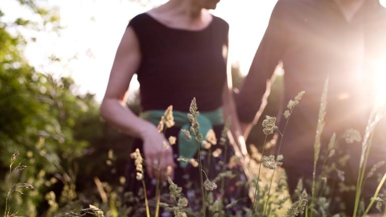 Ein Paar geht im Sonnenschein durch die Natur spazieren.