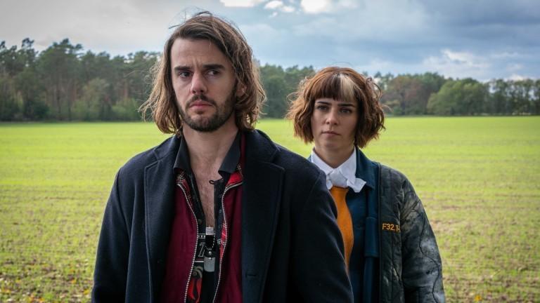 Zwei Schauspieler aus dem Film The Mopes stehen hintereinander auf einer Wiese.