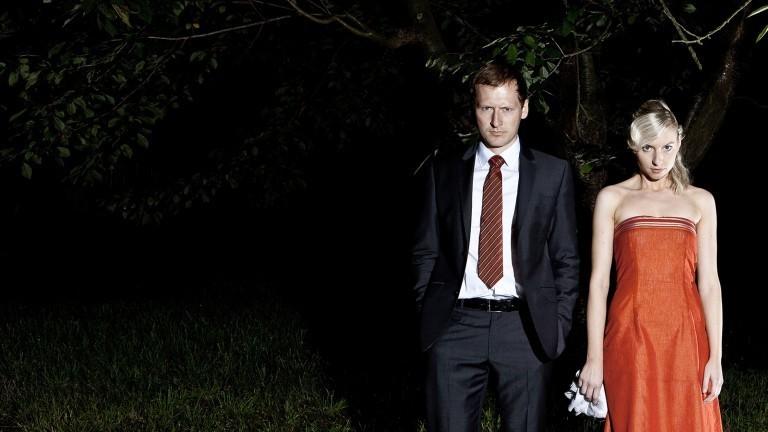 Paar im Partydress vor dunklem Hintergrund - beide gucken skeptisch.