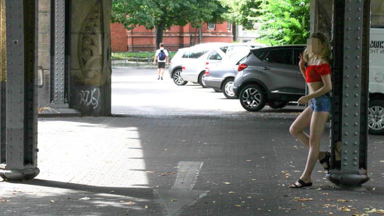 Eine Frau steht angelehnt an einen Brückenpfeiler und raucht