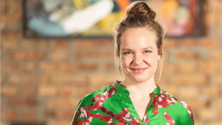 Nathalie Stüben im Portrait. Sie hat die Haare hochgesteckt, lächelt und trägt ein auffälliges grünes Oberteil.