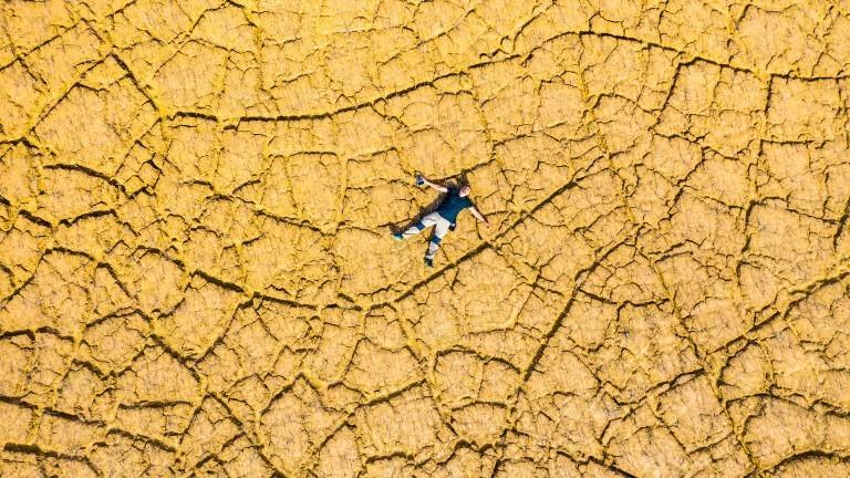Ein Mann liegt auf ausgetrocknetem Boden. Dürre.