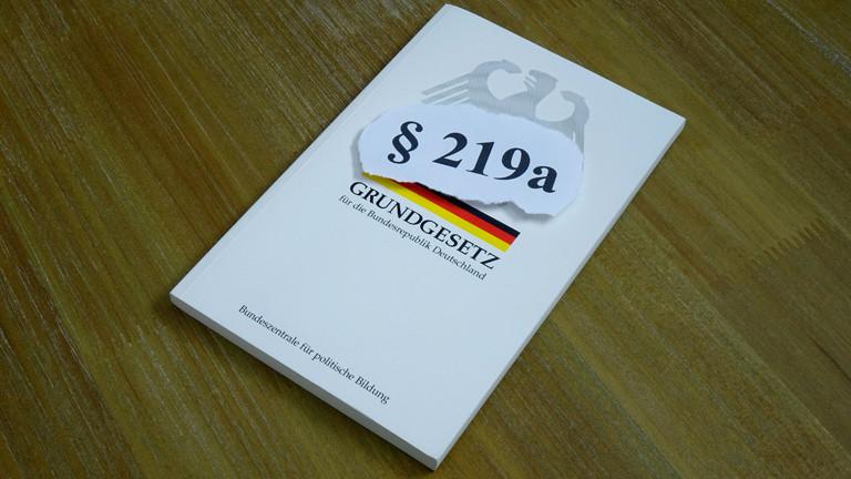 """Ein Zettel mit der Aufschrift """"Paragraf 219a"""" liegt auf einer Ausgabe des Grundgesetzes"""