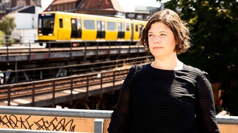 Julia Friedrichs, Reporterin, im Hintergrund fährt eine gelbe Straßenbahn vorbei