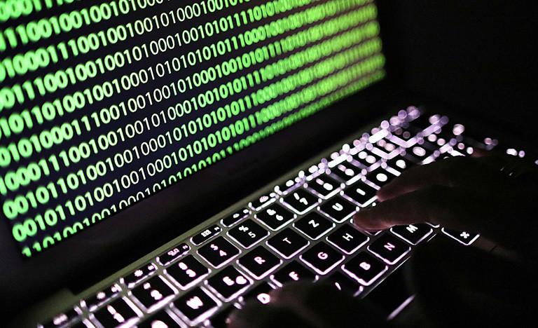 Ein Laptop auf dem der Binärcode zu sehen ist.