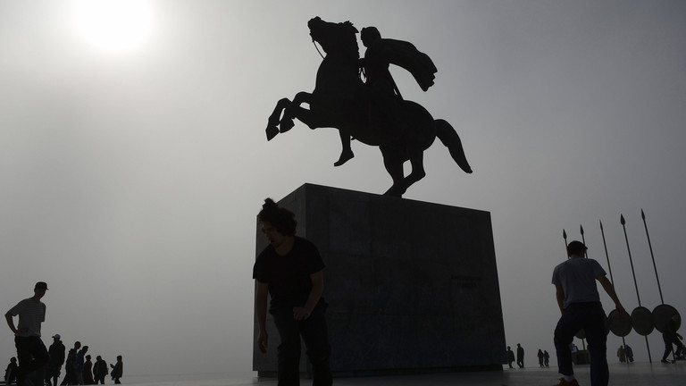 Silhoutte von Menschen und Skatebordern an der Alexander der Große Statue in schwerem Nebel an der Küste der Stadt Thessaloniki