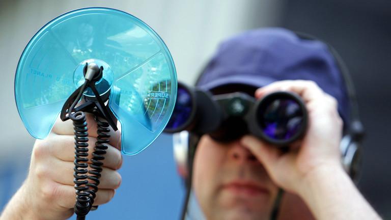 Ein Mann mit Fernglas und Richtmikrofon