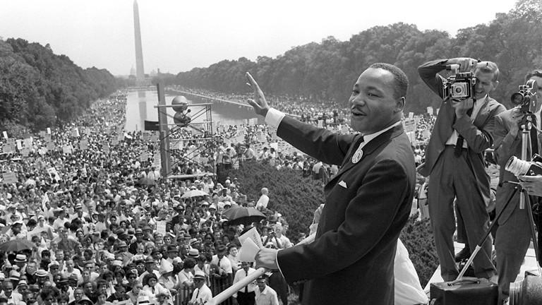 Der US-Bürgerrechtler Martin Luther King winkt bei einer Kundgebung von der Lincoln-Gedächtnisstätte in Washington aus seinen Anhängern zu (im Hintergrund das Washington Monument, Archivfoto vom 28.08.1963).