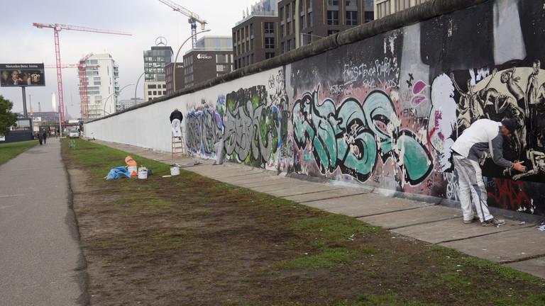 Arbeiter entfernen Graffitis an der Rückseite der East Side Gallery. Sie streichen die ehemalige Mauer für den bevorstehenden Jahrestag des Mauerfalls. Sie soll als Projektionsfläche genutzt werden.