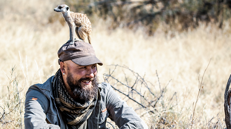 Ein Erdmännchen sitzt auf dem Kopf des Wildtier-Fotografen Christoph Tänzer