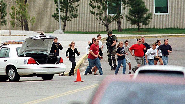 Schüler und Lehrer rennen aus einer Schule