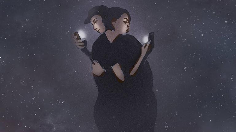 Ein Paar umarmt sich - jeder schaut dabei auf sein Handy.