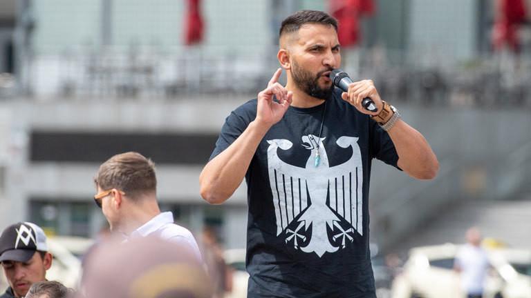 Mann bei einer Kundgebung mit Reichsadler auf dem Shirt