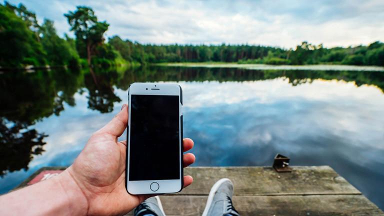 Ein Mann nutzt ein Smartphone am See