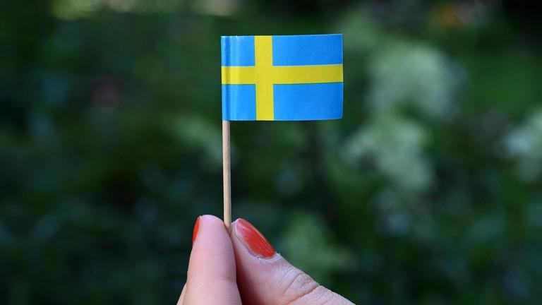 Finger mit rotlackierten Nägeln halten eine schwedische Fahne aus Papier mit Zahnstocher