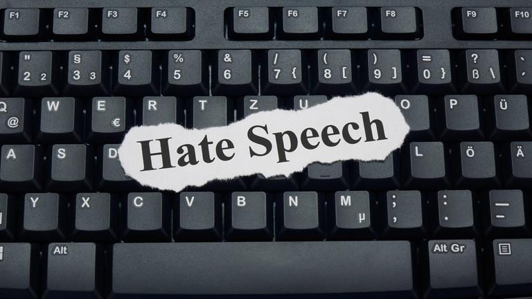 """Zettel, auf dem """"Hate Speech"""" steht auf einer Tastatur"""