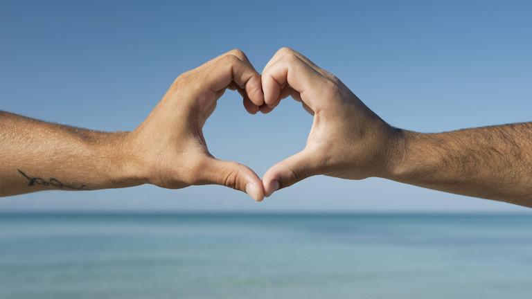 Zwei Männerhände, die ein Herz formen. Im Hintergrund das Meer
