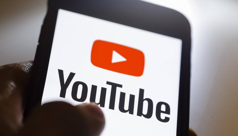 Hand, die ein Smartphone hält, auf dem Youtube geöffnet wird