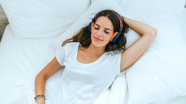 Frau mit Kopfhörern auf einem Bett liegend