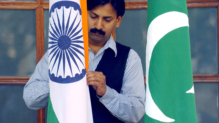 Mann mit einer indischen und einer pakistanischen Flagge