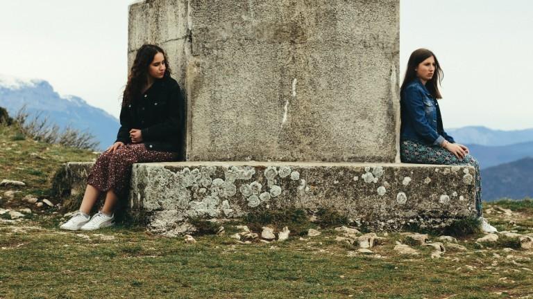 Zwei Frauen sitzen am Fuße eine Monuments. Die Frau auf der linken Seite schaut rüber zu der Frau auf der rechten Seite.
