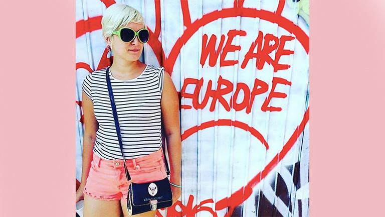 """Eine Frau steht vor einem Graffiti """"We are Europe"""""""