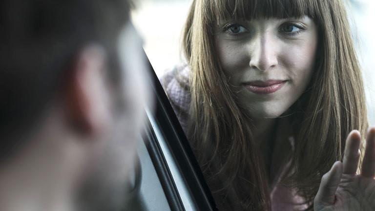 Frau blickt durch eine Fensterscheibe zu einem Mann.