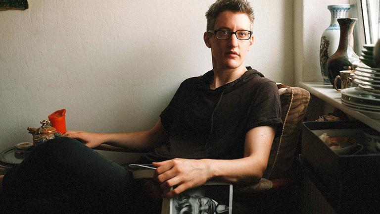 Linus Giese beim Lesen eines Buchs