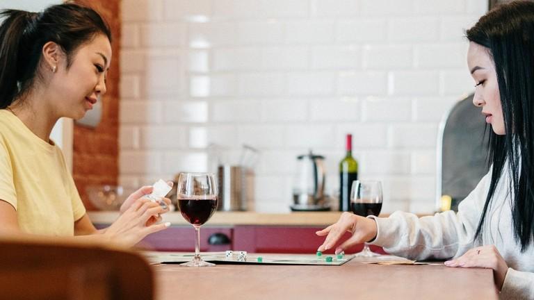 Zwei Frauen sitzen in einer Küche mit einem Glas Wein und einem Brettspiel.