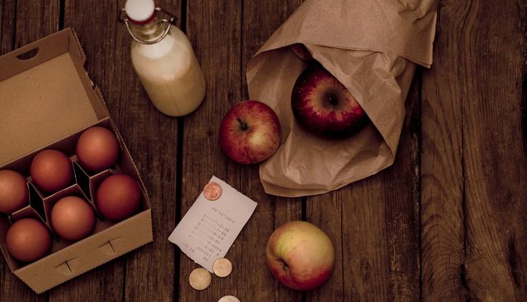 Auf einem Holztisch liegen eine Tüte mit Äpfeln, ein karton mit Eiern, eine Flasche Milch, ein Kassenbon und Wechselgald