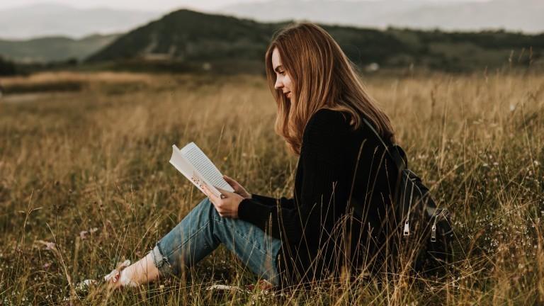 Eine junge Frau sitzt draußen in der Natur mit einem Buch in den Händen.