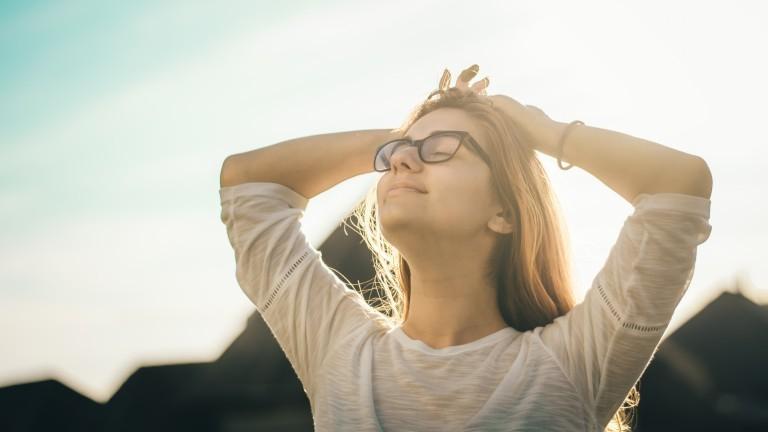 Eine Frau verschränkt die Häne hinterm Kopf und streckt den Kopf mit geschlossenen Augen zum Himmel.