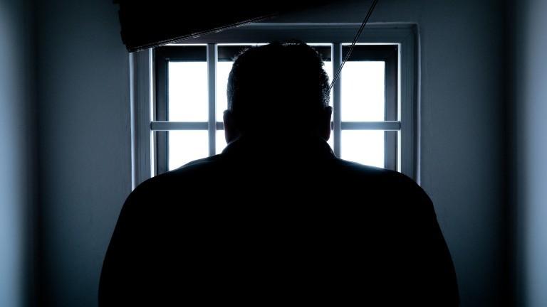 Silhouette eines Mannes, der vor einem vergitterten Fenster steht.