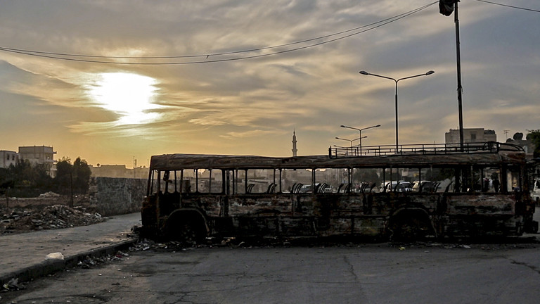 Zerstörter Bus vor einer Stadtkulisse