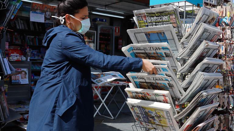 Frau mit Mundschutz an einem Zeitungsstand