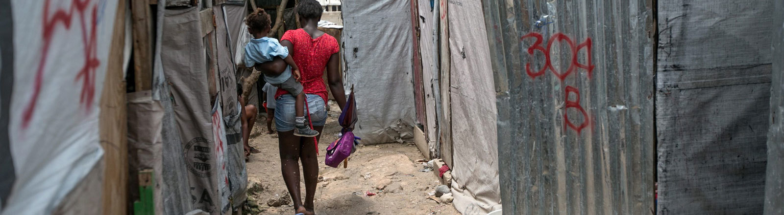 Frau geht durch ein Camp.